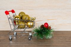 Golden baubles in shopping trolley, christmas sale. Concept Royalty Free Stock Image