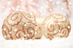 Golden baubles and snow Stock Photos