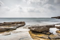 The golden bay. Long exposure seascape landscape of a golden rocky bay in the Mediterranean on a cloudy day during summer time stock image