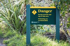 Sign at Wharariki Beach warning of swimming dangers. Golden Bay, New Zealand - 26 August, 2017: Sign at Wharariki Beach warning of swimming dangers royalty free stock photos
