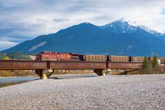Golden, BC, CANADA - OCT 23, 2017: Train passing by the town of. Golden, with the Canadian Rockies in the background, taken from the town of Golden, British royalty free stock photos