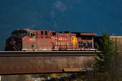 Golden, BC, CANADA - OCT 23, 2017: Train passing by the town of. Golden, with the Canadian Rockies in the background, taken from the town of Golden, British royalty free stock images