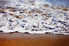 Golden beach. Wave in focus and golden sand royalty free stock photos