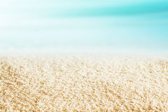 Golden beach sand texture on a tropical beach. Background texture of golden sand on a deserted tropical beach on a beautiful hot summer day with a blue ocean and stock image