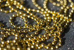 Golden beads on a black background. Royalty Free Stock Photos