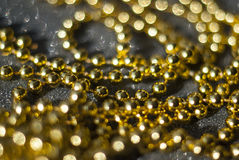 Golden beads on a black background. Stock Image