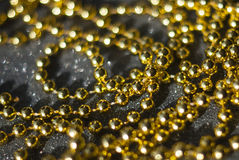 Golden beads on a black background. Royalty Free Stock Images
