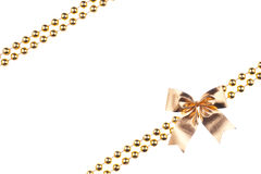 Golden beads with bow  on white background Royalty Free Stock Photography