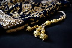 Golden beads and gold embroidery. Handcrafted golden beads and gold and pearl embroidery. Indian clothing detail Royalty Free Stock Image