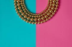 Golden beads on pink blue background. Golden beads lay on pink blue background Stock Photo