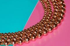 Golden beads on pink blue background. Golden beads lay on pink blue background Royalty Free Stock Image