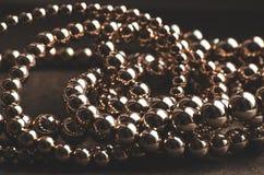 Golden beads necklace on dark background. Golden beads necklace on dark brown background Stock Images