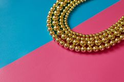 Golden beads on pink blue background. Golden beads lay on pink blue background Royalty Free Stock Photography