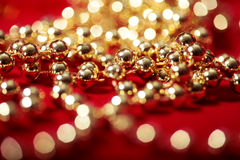 Golden beads on red with blurred lights bokeh Royalty Free Stock Photo