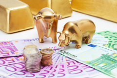 Golden bear, bull figurines with euro coins  gold bars on fanned Royalty Free Stock Images