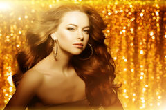 Golden beautiful fashion woman, model with shiny  healthy long v Royalty Free Stock Photo