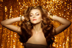 Golden beautiful fashion woman, model with shiny  healthy long v Stock Image