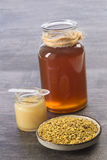 Golden bee pollen iin a cup with royal jelly and honey in jar glass Stock Photos
