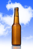 Golden beer with frost bubbles in brown glass bottle on blue sky royalty free stock photo