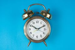 Golden bell alarm clock isolated on blue background. Time concept Royalty Free Stock Images