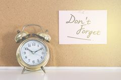 Golden bell alarm clock and a note writen DON`T FORGET on a cork board. Time management, memo and business concept Stock Image