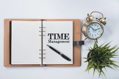 Golden bell clock, green plant and blank notebook with TIME MANAGEMENT word on white flat lay. Time management concept Royalty Free Stock Photography