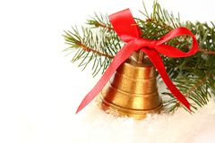 Golden bell with red bow and branch of christmas tree Royalty Free Stock Photo