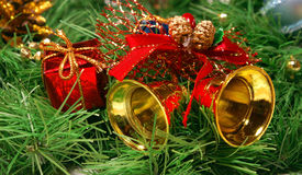 Golden bells against Xmas tree branch Royalty Free Stock Photography