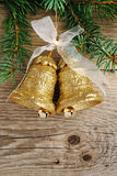 Golden bells on christmas tree on wood Royalty Free Stock Images