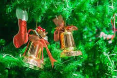 Golden bells and sock ornament on Christmas Tree Stock Photography