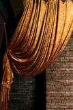 Golden big curtain on brick wall Stock Images