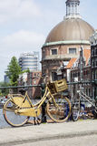 Golden bike with basket with some building in Amsterdam Stock Images