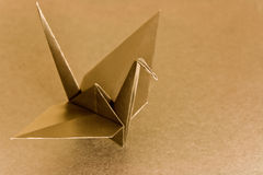 Golden bird. An origami bird on a metallic colour background. Shallow depth of field. Focus on the head of the bird Stock Images