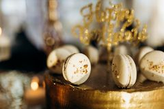 A golden birthday cake is decorated with macaroni royalty free stock photo