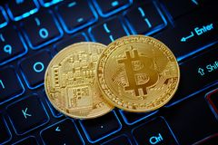 Golden Bitcoin as crypto currency. On top of illuminated keyboard royalty free stock photos