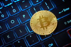 Golden Bitcoin as crypto currency. On top of illuminated keyboard royalty free stock photo