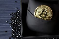 Golden bitcoin in a black box. Gold coin of cryptocurrency. stock photo