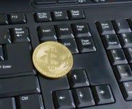 Golden bitcoin on black keyboard. Closeup Stock Photo