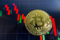 Golden Bitcoin on black laptop screen with stock exchange graph. Background. Digital money concept Stock Image