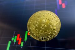 Golden Bitcoin on black laptop screen with stock exchange graph. Background. Digital money concept Royalty Free Stock Photos