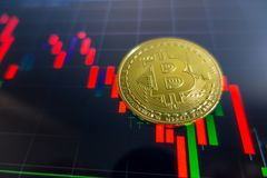 Golden Bitcoin on black laptop screen with stock exchange graph. Background. Digital money concept Stock Photography