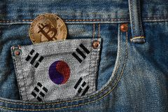 Golden BITCOIN & x28;BTC& x29; cryptocurrency in the pocket of jeans with stock photos