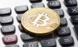 Golden bitcoin on calculator Royalty Free Stock Photography