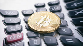 Golden bitcoin on calculator Stock Photography