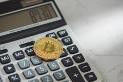 Golden bitcoin with calculator on white background.  Stock Images