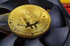 Golden bitcoin on the central processing unit fan background closeup. Cryptocurrency virtual money Royalty Free Stock Photography