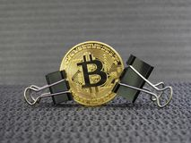 Golden Bitcoin clamped Royalty Free Stock Photography