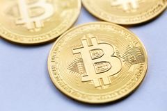 Golden Bitcoin close up, next to other coins out of focus stock photography