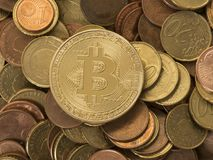 Virtual money versus old money. Golden bitcoin coin on a background with euro coins Royalty Free Stock Image