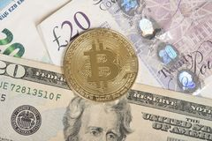 Bitcoin and dollar, pound and euro paper money. Golden bitcoin coin on a background with euro, dollar and british pound paper money Stock Photography